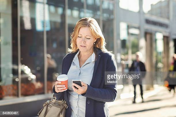Businesswoman using mobile phone and holding disposable coffee cup while walking on sidewalk