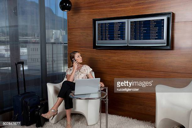 Businesswoman using cell phone in airport lounge