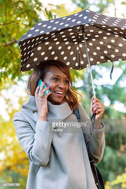 Businesswoman Using Mobile Phone in Park, London UK