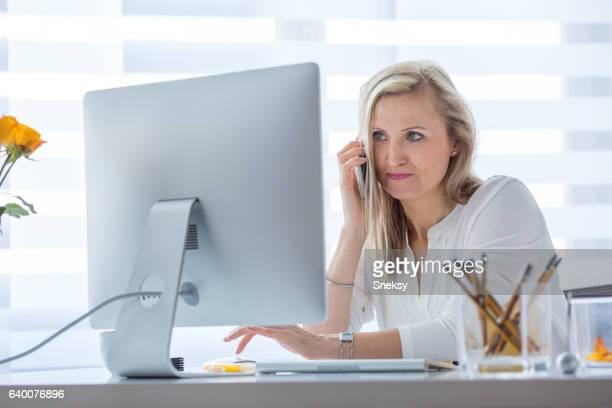 Businesswoman using phone in modern office