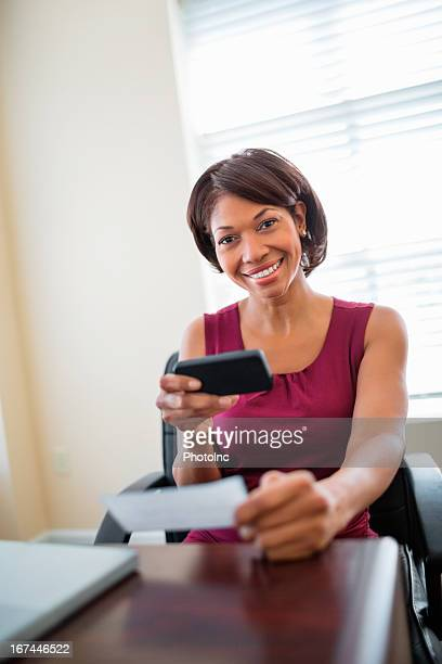 Businesswoman Using Phone To Deposit Check