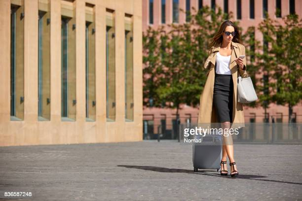 Businesswoman using phone while pulling luggage