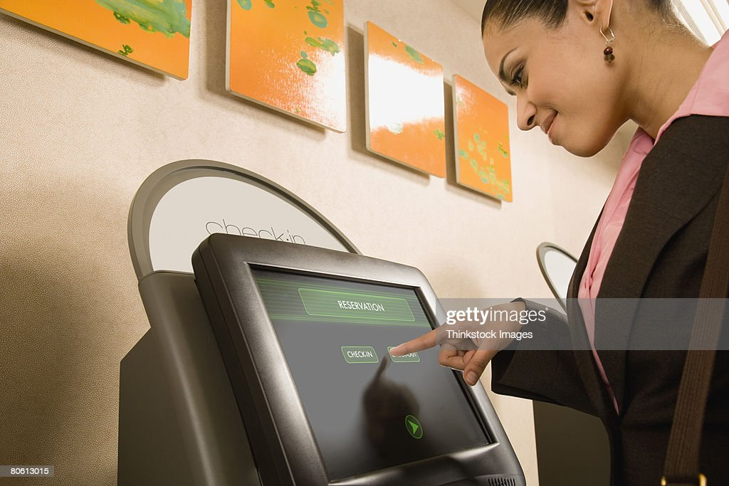 Businesswoman using self check-in terminal