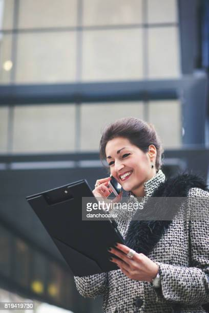 Businesswoman using smart phone outdoors and smiling