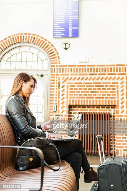 Businesswoman using smart phone while sitting at waiting area in railway station
