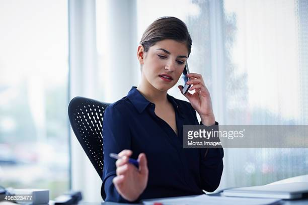 Businesswoman using smart phone while working