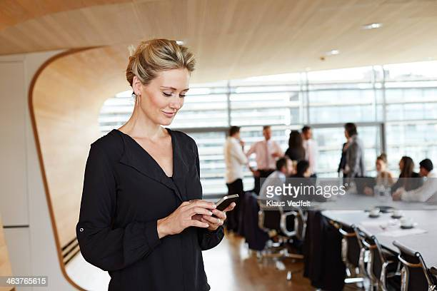 Businesswoman using smartphone in conference room
