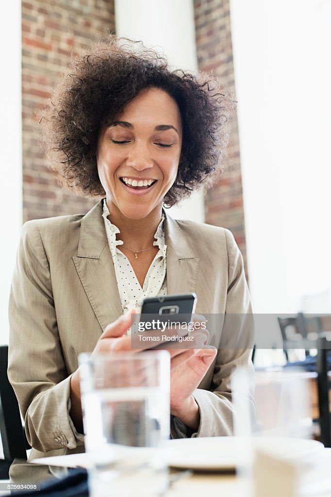 Businesswoman using smartphone in restaurant : Stock Photo