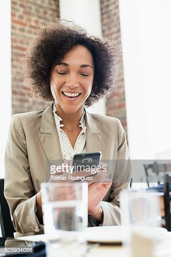 Businesswoman using smartphone in restaurant : Stock Photo