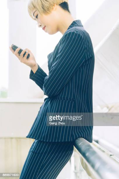 businesswoman using smartphone leaning on railing