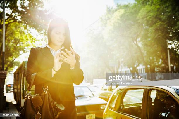 Businesswoman using smartphone waiting for taxi