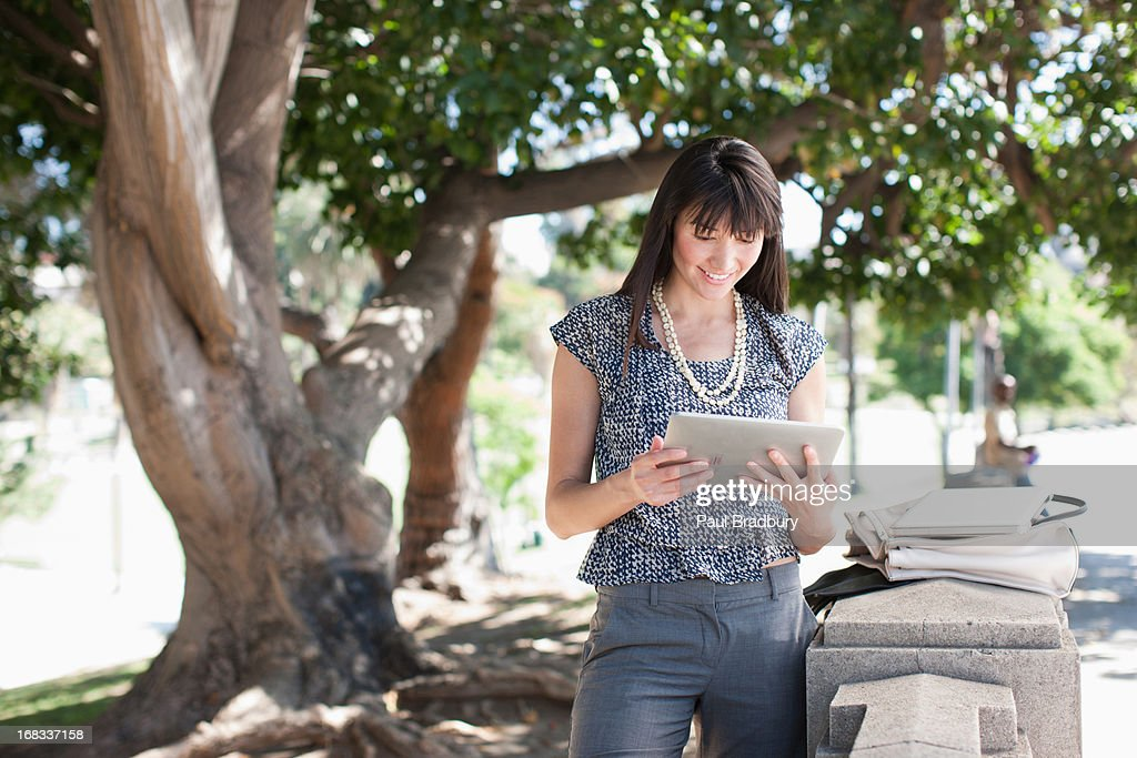 Businesswoman using tablet computer outdoors : Stock Photo