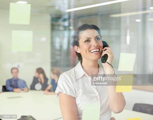 ビジネスウーマンの電話を使用して、お仕事仲間とのミーティング、コンファレンス