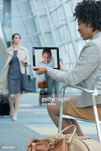 Businesswoman video conferencing with daughter in airport