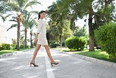 Businesswoman walking across street