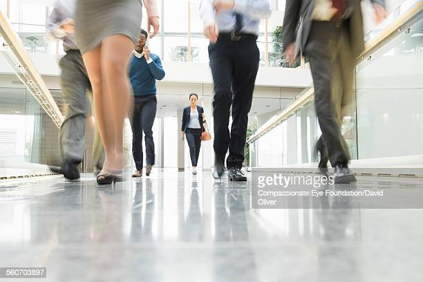 Businesswoman walking along busy walkway