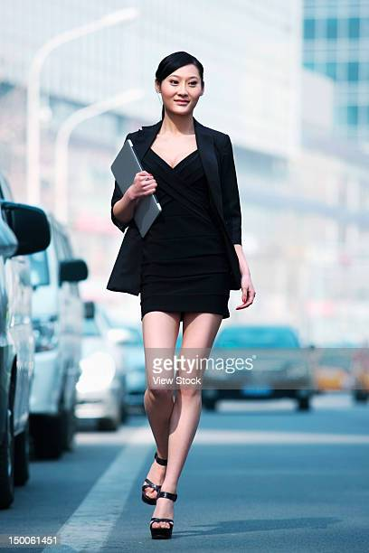 Businesswoman walking along street