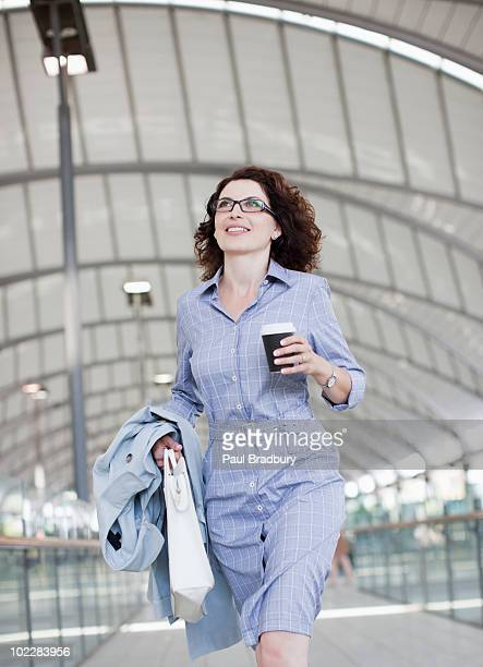 Businesswoman walking and holding coffee