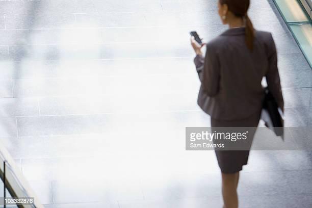 Mulher de Negócios andar, olhar para baixo no telemóvel