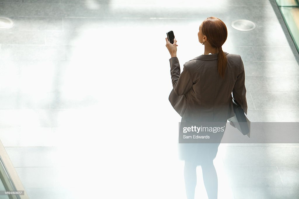 Businesswoman walking and looking down at cell phone : Stock Photo