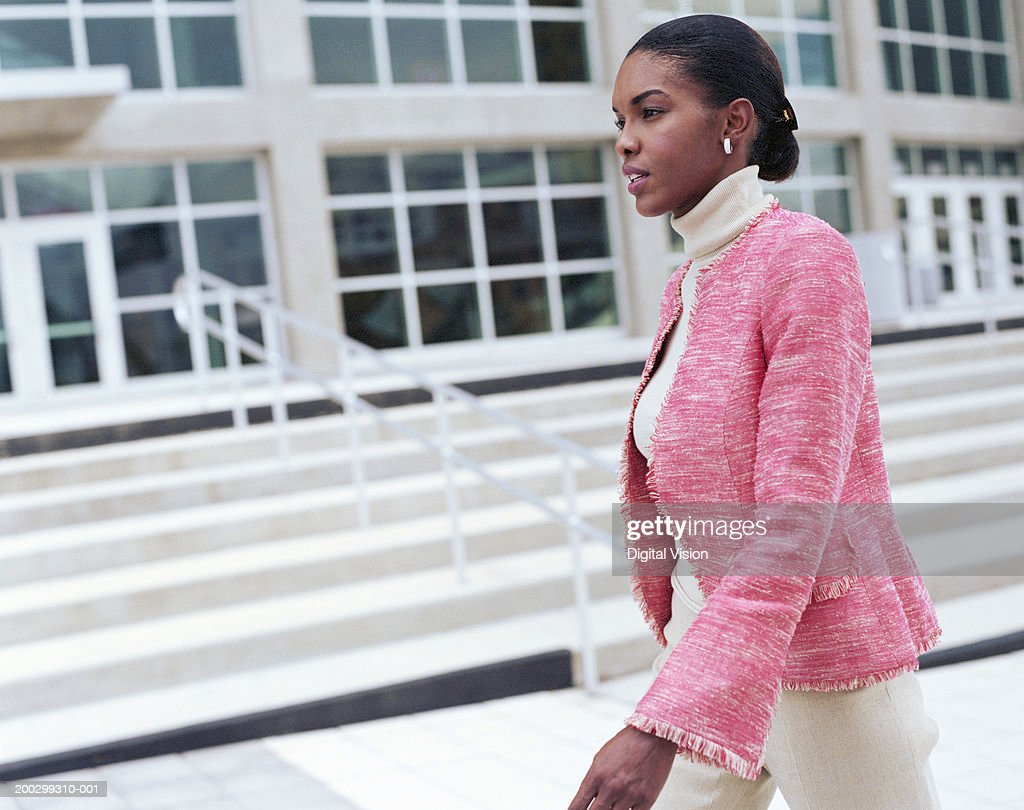 Businesswoman walking by office building, side view