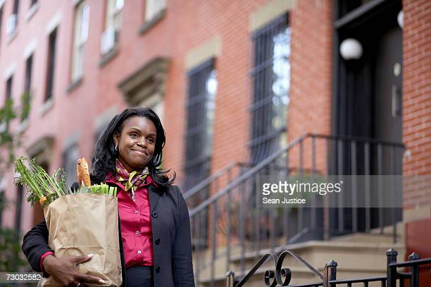 Businesswoman walking home from work carrying groceries