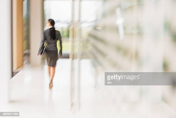 Businesswoman walking in brighlty lit office corridor