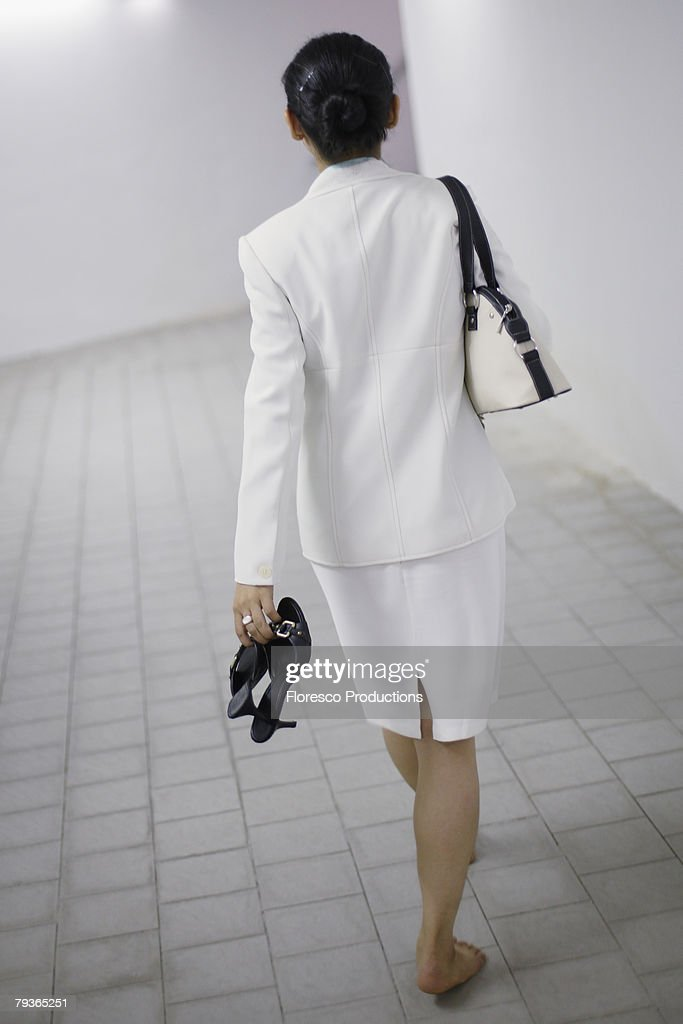 Businesswoman walking in corridor barefoot : Stock Photo