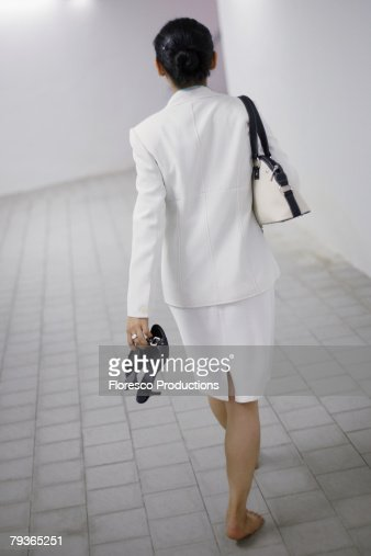 Businesswoman walking in corridor barefoot : Stock Photo