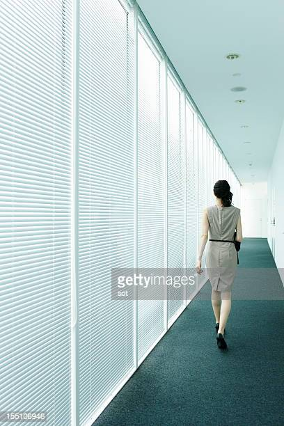 Businesswoman walking in office hallway,rear view