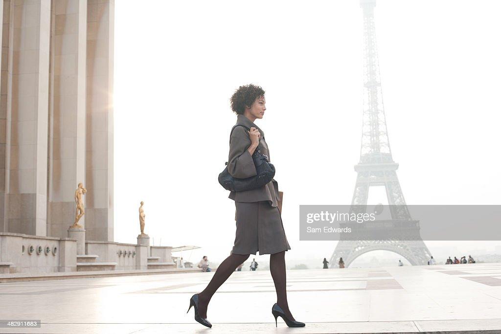 Businesswoman walking in plaza by Eiffel Tower
