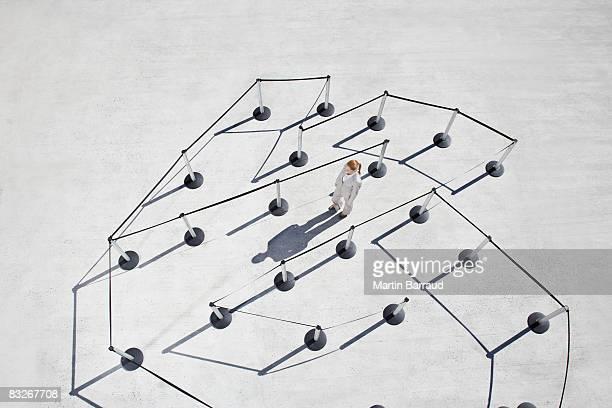 Businesswoman walking maze of cordon posts