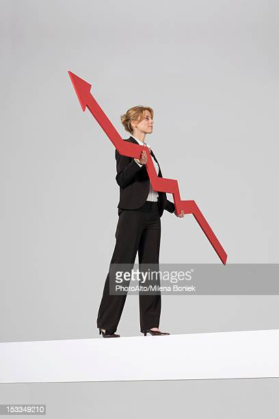Businesswoman walking on balance beam, carrying large arrow indicating profits