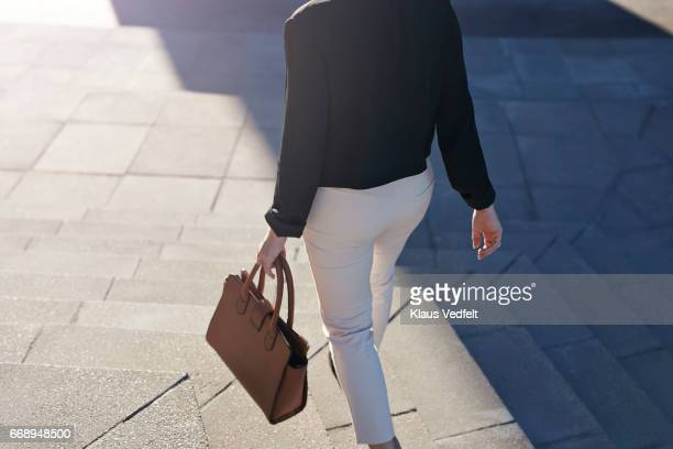 Businesswoman walking on staircase with bag