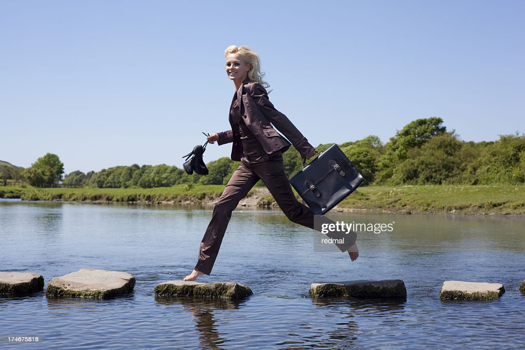 A businesswoman walking on the stepping stones successfully