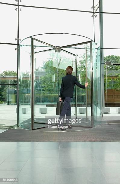 Businesswoman walking through revolving door
