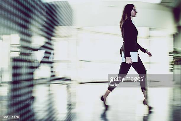 Businesswoman Walking Through The Office Corridor and Carrying Digital Tablet