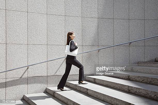 Businesswoman walking up steps