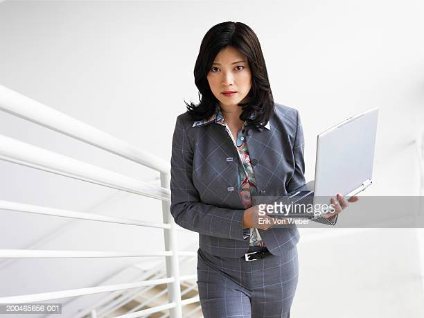 Businesswoman walking upstairs holding laptop, portrait