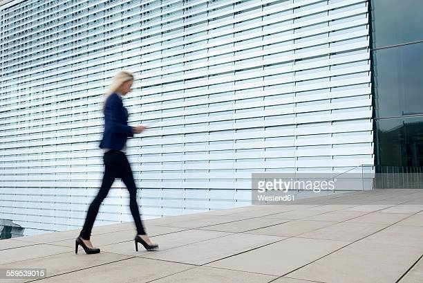 Businesswoman walking with digital tablet