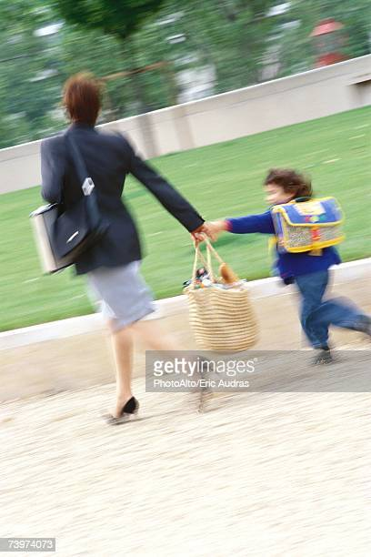Businesswoman walking with son, blurred motion