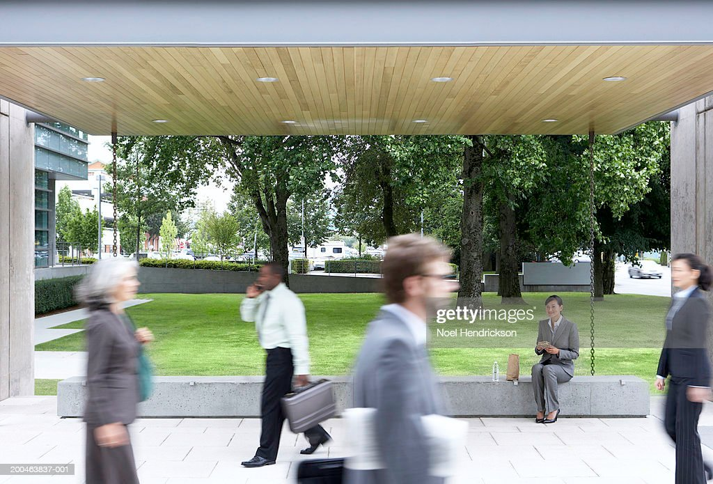 Businesswoman watching colleagues pass by, outdoors (blurred motion) : Stock Photo