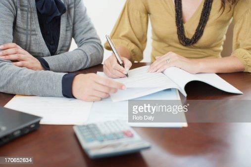 Businesswoman watching woman sign paperwork