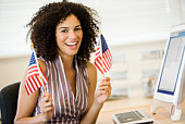 Businesswoman waving American flags at desk