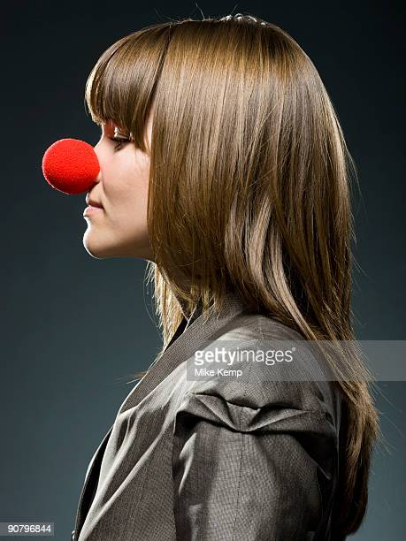 businesswoman wearing a red clown nose