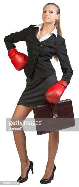 Businesswoman wearing boxing gloves standing akimbo : Stock Photo