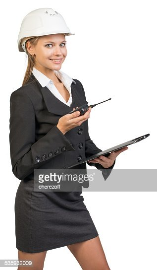 Businesswoman wearing hard hat holding clipboard and walkie talkie : Stock Photo