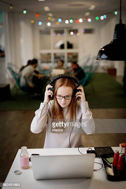 Businesswoman wearing headphones while working late on laptop in creative office