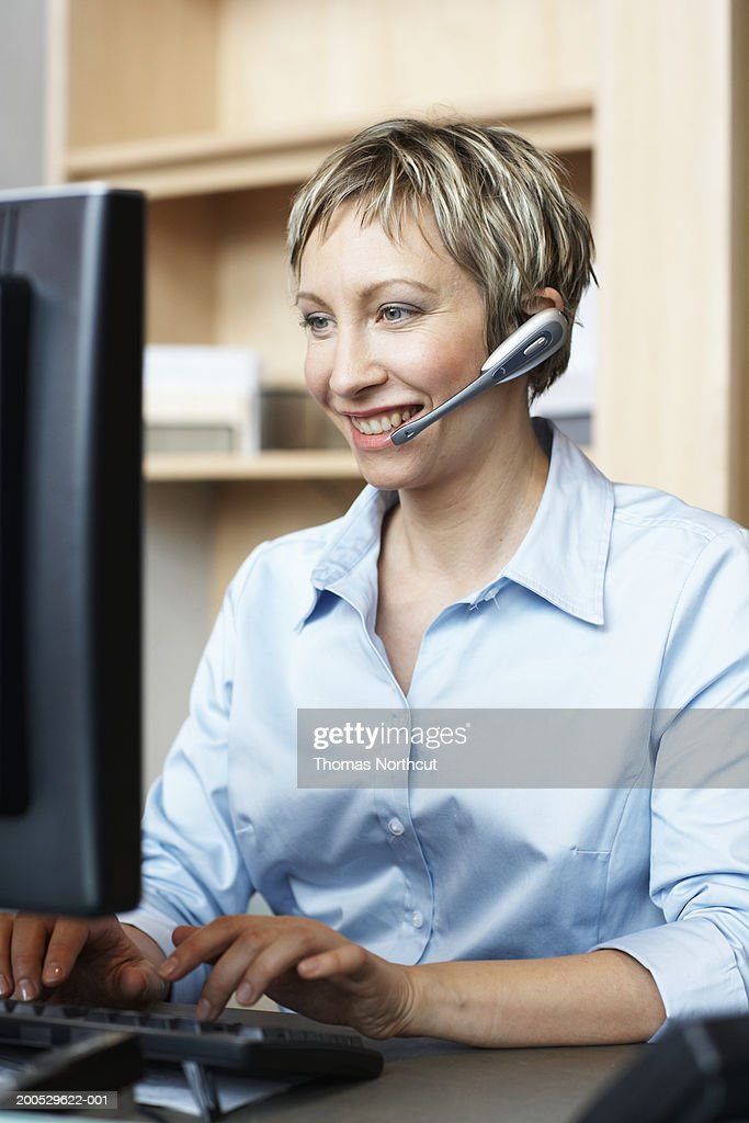 Businesswoman wearing headset and using computer, smiling : Stock Photo
