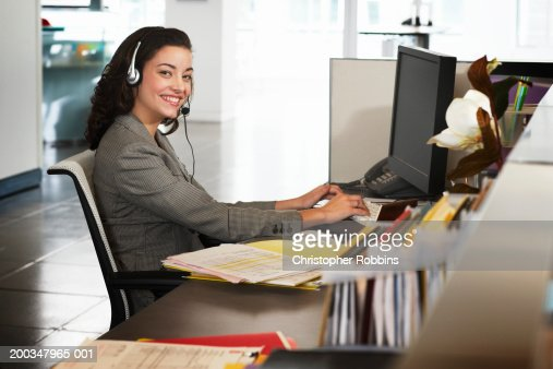 Businesswoman wearing headset at desk, smiling, portrait : Stock Photo